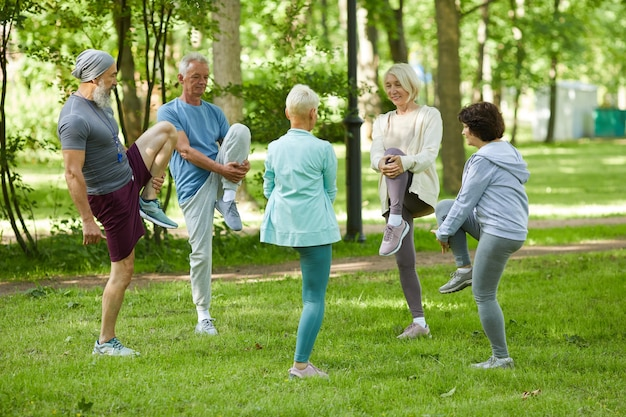 Group of modern senior people spending sunny morning in park doing stretching exercise