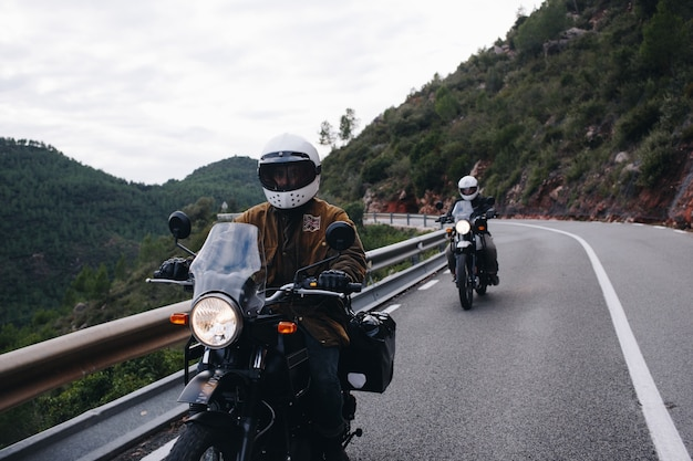 Gruppo di motociclisti su strada di montagna