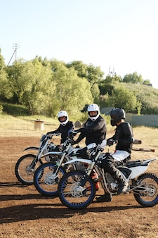 Group of motorcyclists sitting on motorbikes and talking to each other before off-road competition