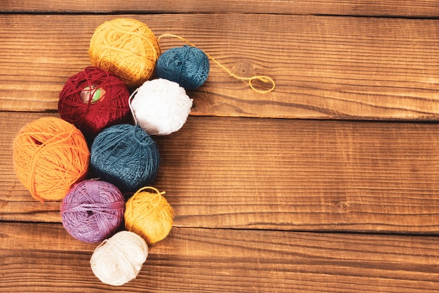Group of multi-colored woolen clews on a wooden background.