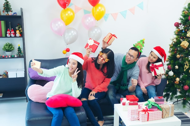 Group of multi-ethnic coworkers taking selfie in santa hats at office party,