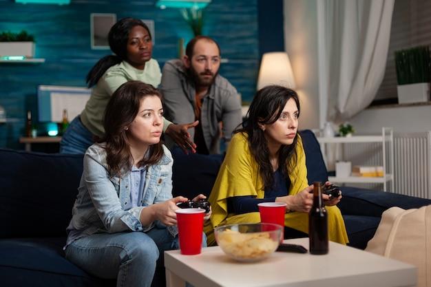 온라인 전투 경쟁에서 컨트롤러를 사용하여 비디오 게임을 하는 다민족 친구들을 그룹화합니다. 사람들은 재미 있고, 맥주를 마시고, 늦은 밤 거실 소파에 앉아 사교 활동을 하고 있습니다.