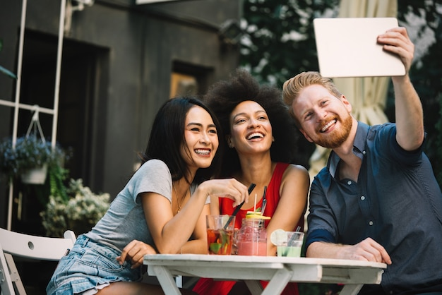 Group of multi ethnic friends talking and having fun at cafe outside