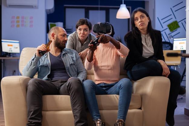 Gruppo di amici multietnici che usano occhiali vr per divertirsi dopo il lavoro in ufficio