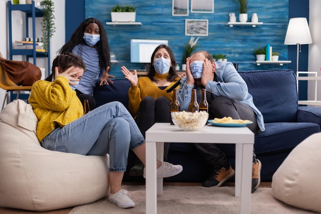 Group of multi ethnic friends watching a horror movie on tv being afraid wearing face mask to prevent infection with covid 19 during global pandemic having fun sitting on couch and