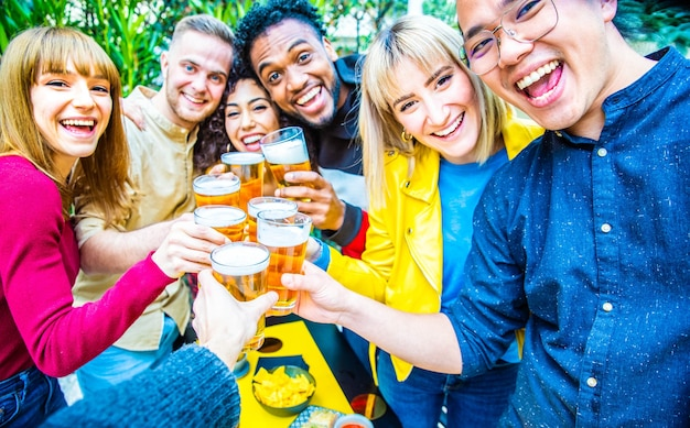 Group of multicultural friends drinking and toasting beer at brewery bar restaurant