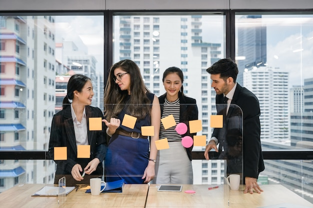 Group of multiethnic business colleagues analyzing and discussing about business idea with sticky note on board in modern office