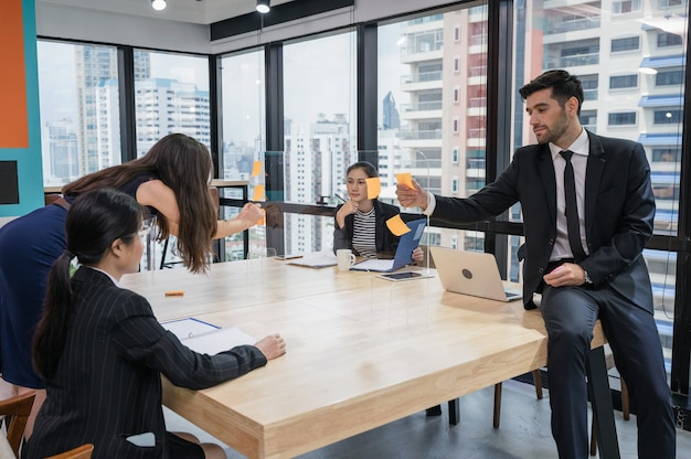 Group of multiethnic business colleagues collaboration brainstorming on business idea with sticky note on board in modern office