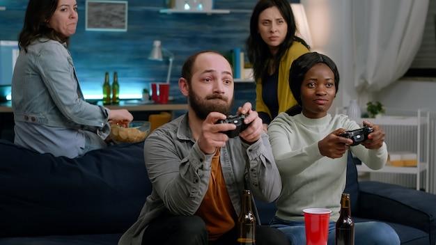 オンラインバトルコンペティションの人々の間にコントローラーを使用してビデオゲームをプレイする多民族の友人をグループ化します...