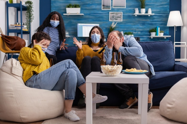 Group of multiethnic friends watching a horror movie on tv being afraid, spending weekend together wearing face mask to prevent infection with covid 19 during global pandemic enoying beer and chips