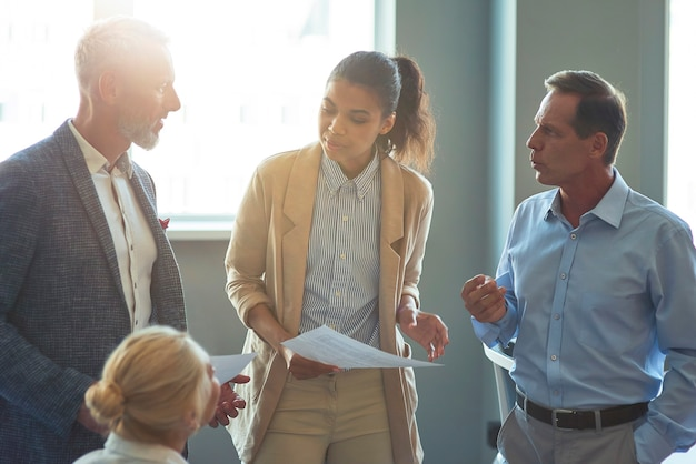 Group of multiracial business people discussing project results analyzing reports while having a