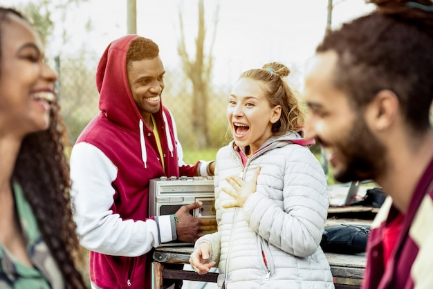 Group of multiracial friend couples having fun time out at park in autumn winter time - youth friendship concept with people together outdoors - focus on blond young woman