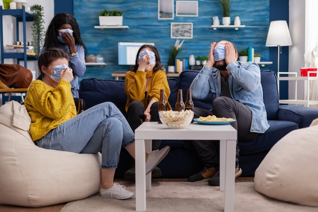 Group of multiracial friends watching horror show on tv enjoying spending time together wearing face mask to prevent infection with covid 19, during global pandemic having fun sitting on couch