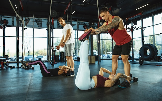 A group of muscular athletes doing workout at the gym