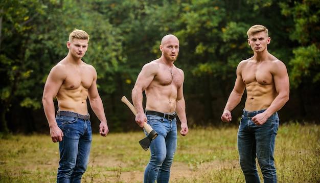 筋肉質の男性を斧でグループ化します。運動男は斧を使用します。野生の男らしさ。同胞団の概念。強さと忍耐力。筋肉の胴体を持つ男性。強い男性の自然の背景。より難しいトレーニングを刺激します。