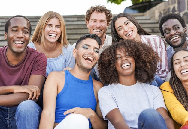 Group of mutliracial  friends smiling on camera while sitting in the city - millennial people enjoy time together outdoor - diversity, friendship and happiness concept