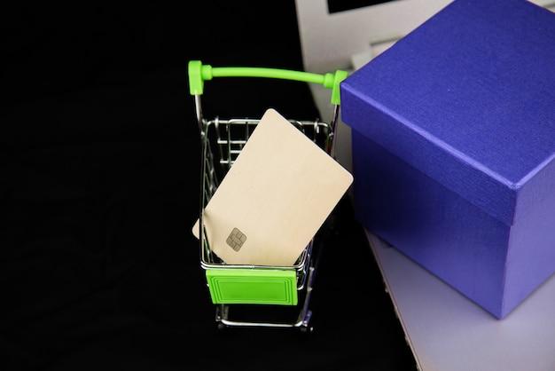グループオブジェクトカレンダー2021とショッピングカートのクレジットカード、暗い背景のラップトップの青いgitfボックス。