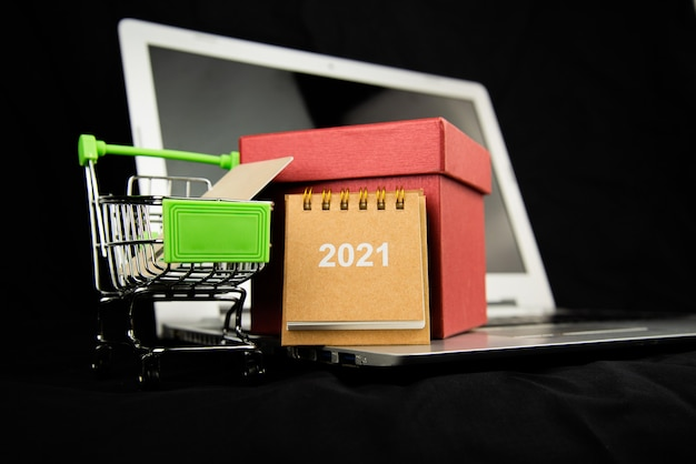 Group object calendar 2021 and credit card in the shopping cart and red gitf box on laptop with dark background.