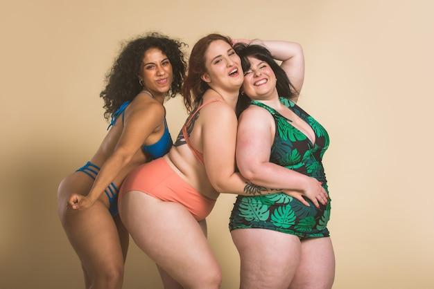 スタジオでポーズをとる3人の特大の女性のグループ