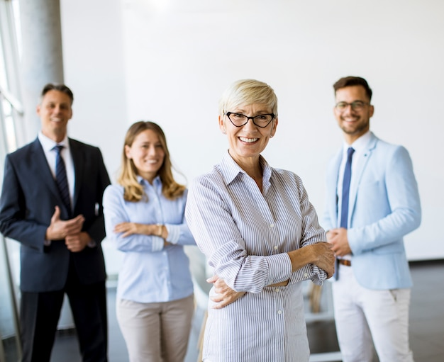 성숙한 여성 탈취 리더와 함께 사무실에서 함께 서있는 기업인의 그룹