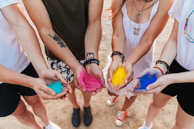 カラフルなホーリーペイントで手を見せて、ビーチで楽しんでいる陽気な若い友人のグループ