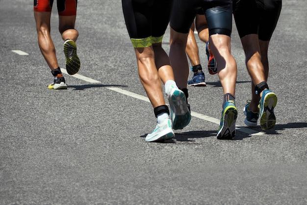 아스팔트 도로를 달리는 활동적인 사람들. 스포츠 마라톤에서 주자의 하체 부분