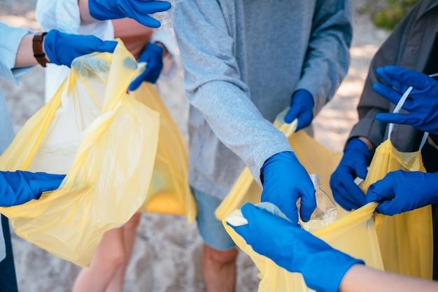 Группа активистов друзей собирает пластиковые отходы на пляже. охрана окружающей среды.