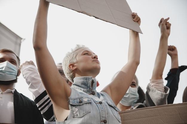 Группа активистов, выступающих с лозунгами на митинге, мужчины и женщины вместе маршируют на митинге в