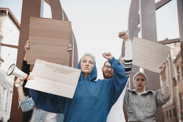 集会でスローガンを掲げる活動家のグループ。抗議で一緒に行進する男性と女性