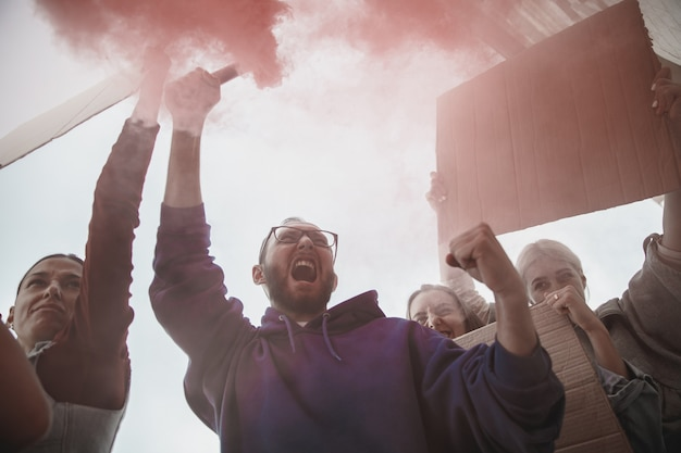 Группа активистов, выступающих с лозунгами на митинге, мужчины и женщины вместе маршируют в знак протеста