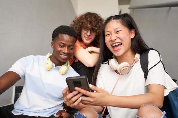 カメラを探している携帯電話中国の女の子を使用してさまざまな民族の思春期の学生のグループ