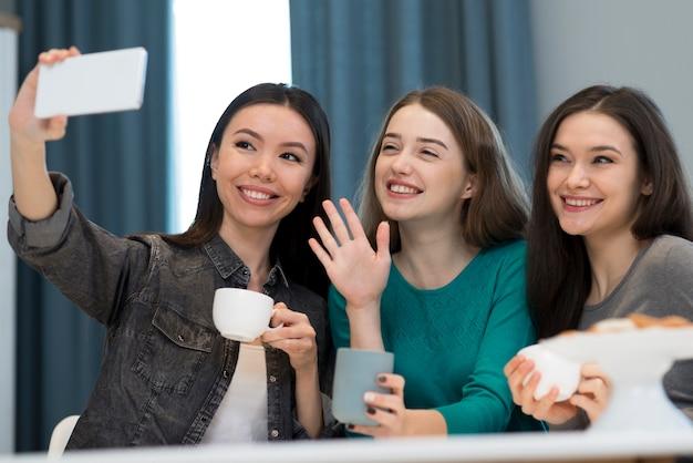Группа очаровательных молодых женщин, делающих снимок вместе