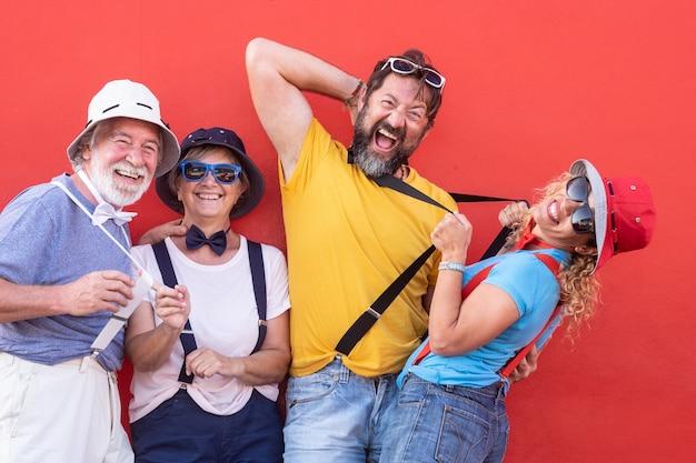 赤い壁に屋外で遊んでいる大人の幸せな人々のグループ。蝶ネクタイとサスペンダーを身に着けたファニーな服装。色、パーティーやお祝いの日でいっぱい