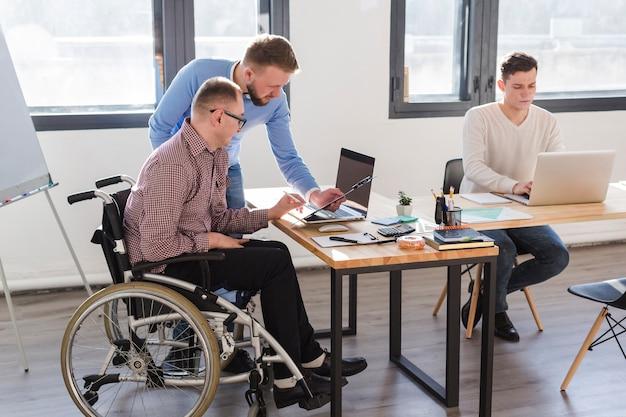 Группа взрослых мужчин, работающих вместе в офисе