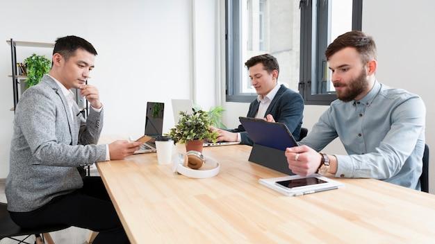 Группа взрослых мужчин, работающих вместе