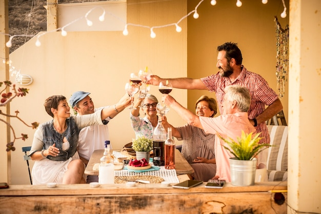 40 歳から 80 歳までのさまざまな年齢の大人のグループが、家のテラスで食事とワインを飲みながら一緒に祝います
