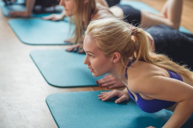 Группа взрослых, выполняющих упражнения для отжимания в тренажерном зале для занятий фитнесом в помещении с ярким световым отблеском над ними