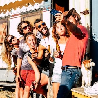 代替的で多様なミレニアル世代の人々のグループは、電話で自分撮り写真を撮り、シーンで古いキャラバンと一緒に野外活動で狂ったように笑って一緒に楽しんで楽しんでいます