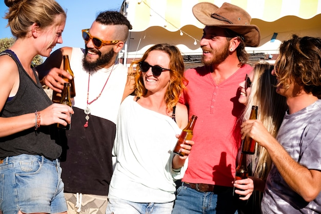 代替の若い白人の人々のグループは、友情と笑顔とビール瓶と一緒に楽しんで楽しんでいます