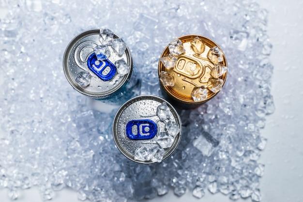 Группа алюминиевых банок во льду, холодный напиток.