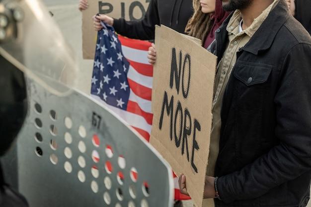 집회에서 정부를 촉구하는 동안 판지 배너를 들고 있는 미국인 그룹, 군중에 맞서 방패를 들고 서 있는 경찰
