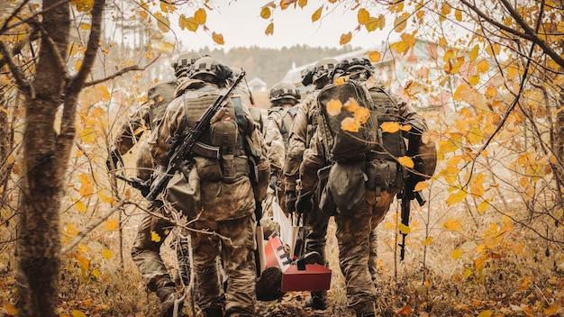 アメリカ兵のグループが負傷した兵士を避難させます。軍事紛争の概念。戦争。ミクストメディア