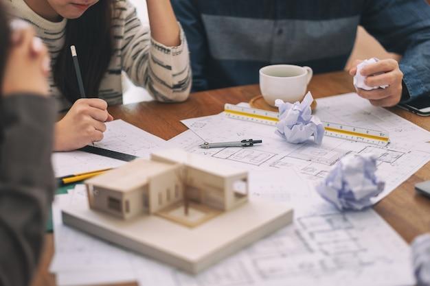 Группа архитекторов чувствуют стресс после работы над моделью архитектуры вместе с чертежной бумагой магазина на столе в офисе