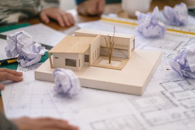 建築家のグループは、オフィスのテーブルに紙を描く店と一緒に建築モデルに取り組んだ後、ストレスを感じます