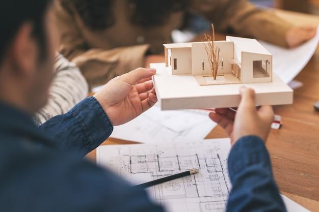 建築モデルを保持し、オフィスのテーブルに紙を描くショップと話し合う建築家のグループ