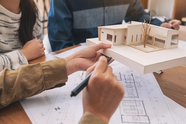 働いて、オフィスのテーブルにショップ画用紙と一緒にアーキテクチャモデルについて議論する建築家のグループ