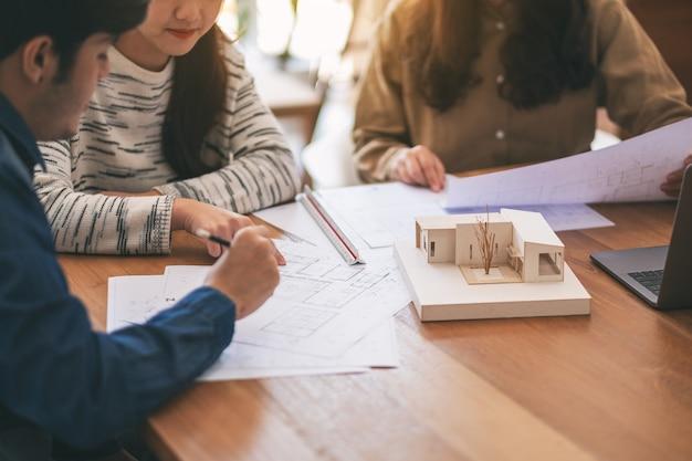 オフィスのテーブルに紙を描く店と一緒に建築モデルについて働いて議論している建築家のグループ