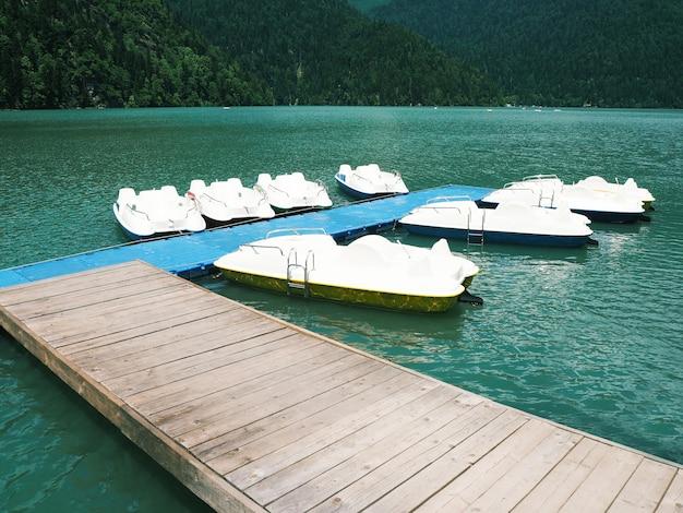 푸른 호수 배경에 고정된 흰색 쌍동선의 그룹입니다. 수상 페달 보트