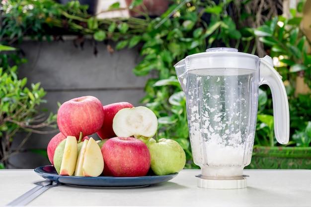 세라믹 접시에 있는 사과와 구아바 과일 그룹은 전기 믹서기로 신선한 사과와 구아바 주스를 만듭니다.