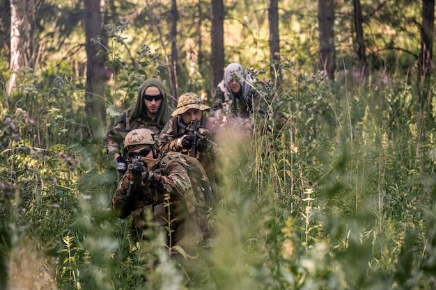조정 된 군사 행동을 수행 하는 동안 숲의 긴 풀을 통해 소총으로 이동 하는 군대의 그룹